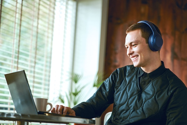 Lifestyle image of man using WH-XB900N headphones to make hands-free calls.