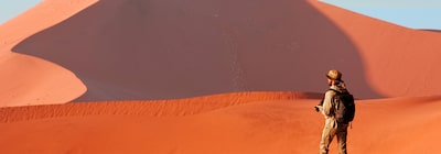 Image of a man facing away from the camera with red-coloured sand dunes in the background