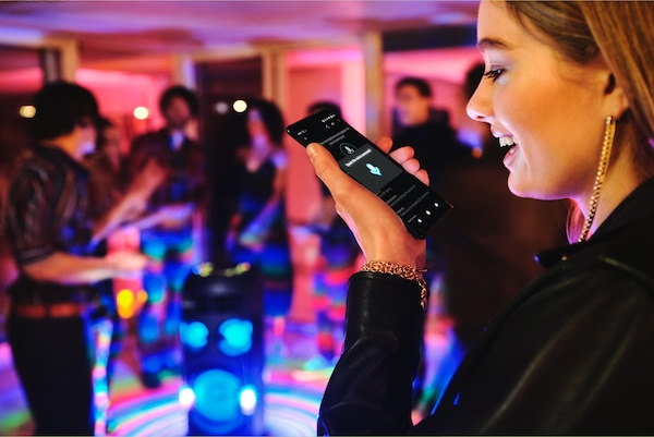 Partygoer using Voice Control via Fiestable on her smartphone